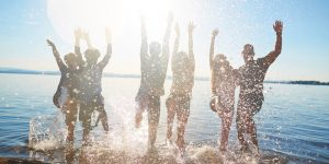 Carefree guys and girls dancing in water at beach party