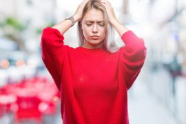 Young blonde woman wearing winter sweater over isolated background suffering from headache desperate and stressed because pain and migraine. Hands on head.